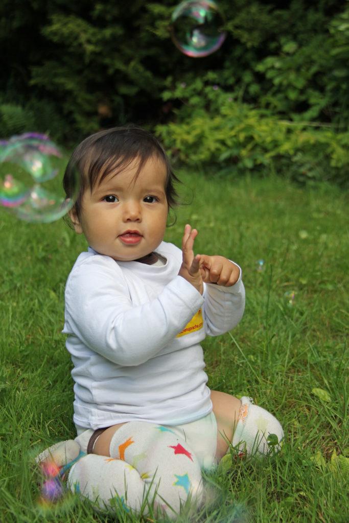 Das Kind zeigt mit der Babyzeichensprache, dass es mehr Seifenblasen sehen möchte