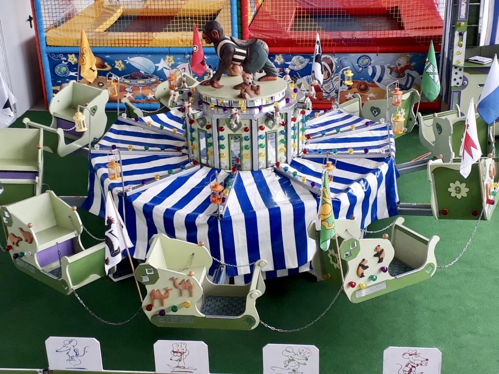 Diverse Spielattraktionen für Kinder wie ein nostalgisches Karussell im Indoor-Spielplatz Sulgen
